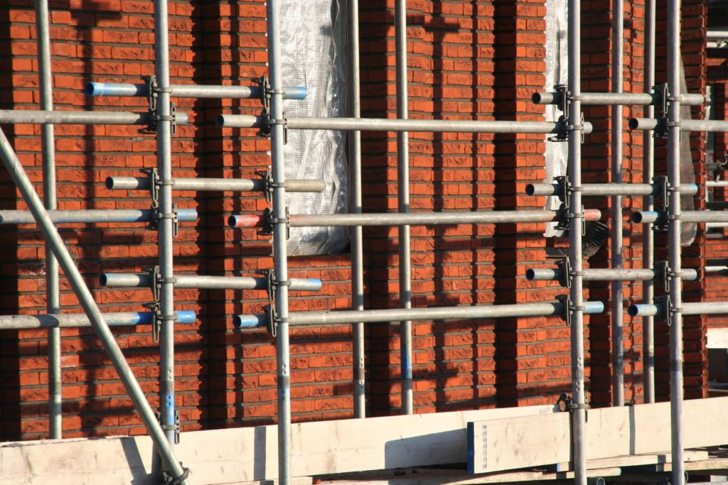 a brick wall with scafoldings